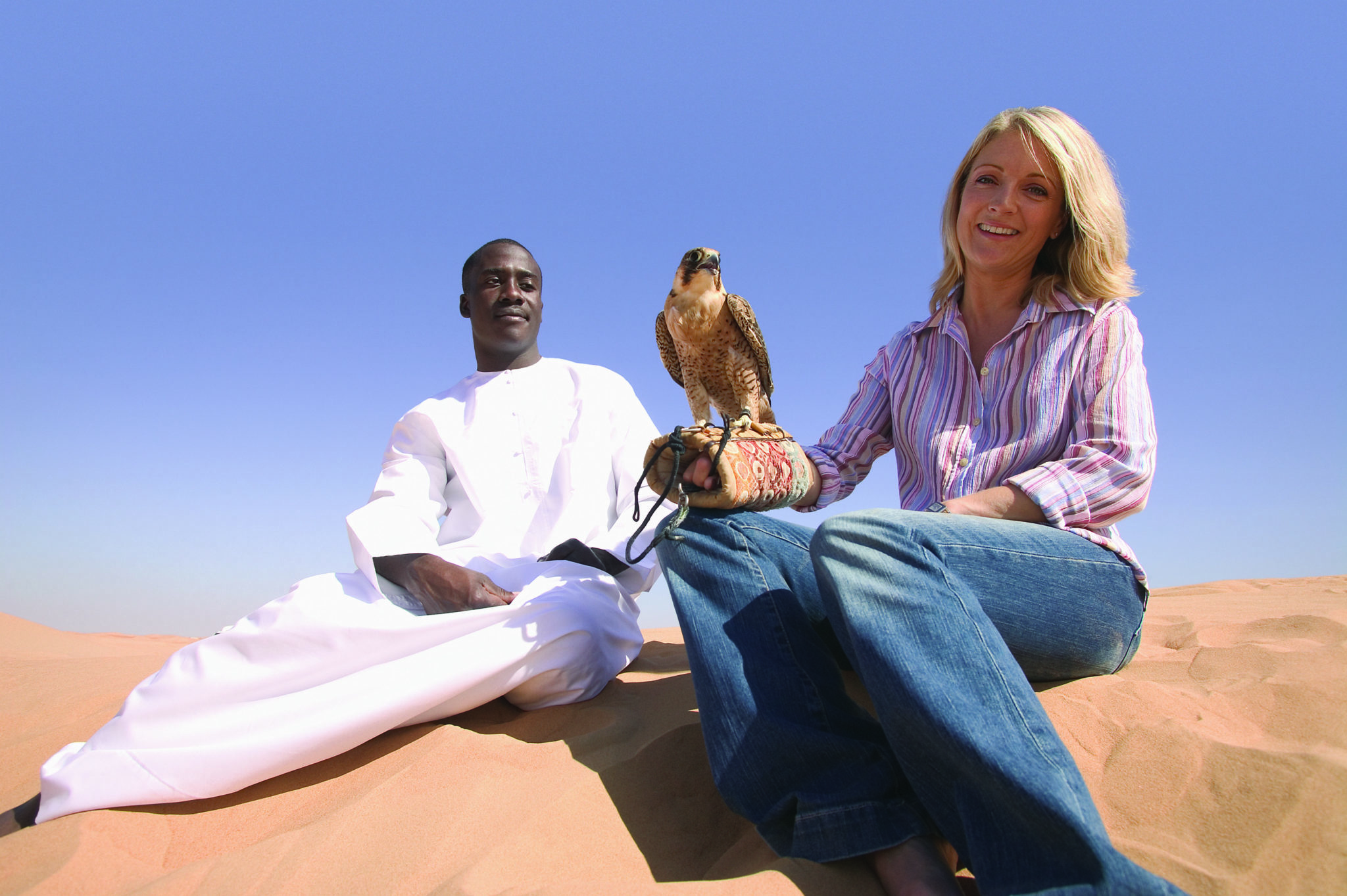 Muslim man in traditional dress and traveller with falcon on arm